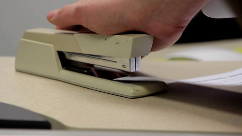 A medium shot of a tan office stapler being used to staple papers in an office Footage