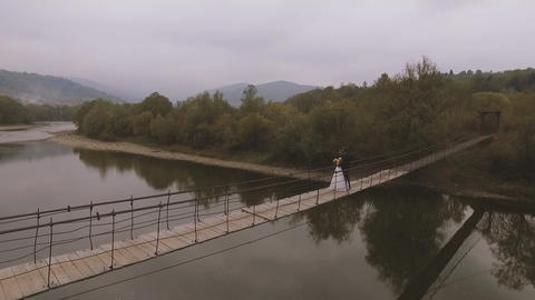 Loving Couple on a Wooden Bridge in the Mountains Footage