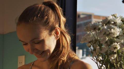 Confused Girl Smiles Smells Flowers on Windowsill Archivo