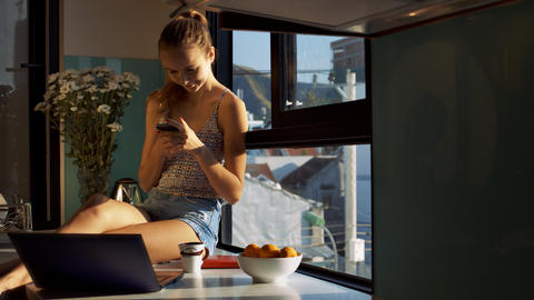Blond Lady Reads Message in Smartphone on Window Sill Live Action
