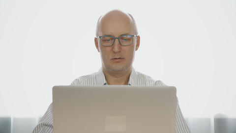 Surprised mature man in glasses looking at laptop screen Footage
