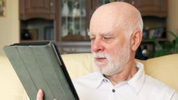 Modern senior man at home using tablet, browsing, reading news. Active modern Footage