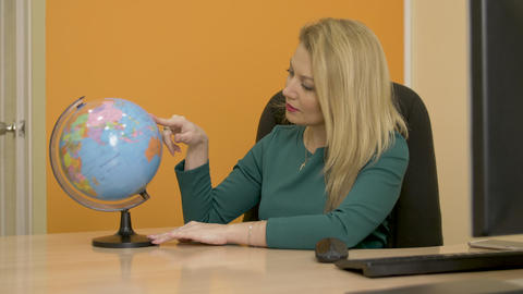 Beautiful woman turning globe map and looking on countries and continents Footage