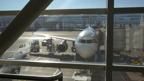 View from the departure lounge of an airplane at a departure gate Live Action
