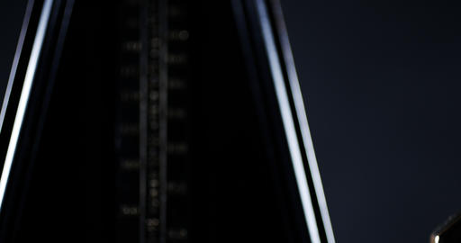 Metronome with golden pendulum beats slow rhythm on the dark background Archivo