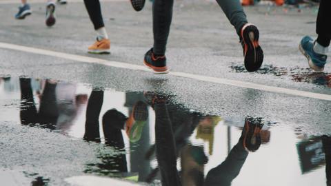 Lots of sportsmen feet running marathon reflecting in puddle Footage