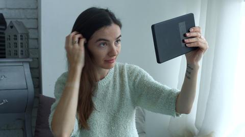 Woman adjusting her hair using tablet as mirror Footage