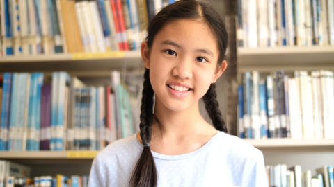 4K Asian teenager student reading a book in school library for inspiration,Shoot Live Action