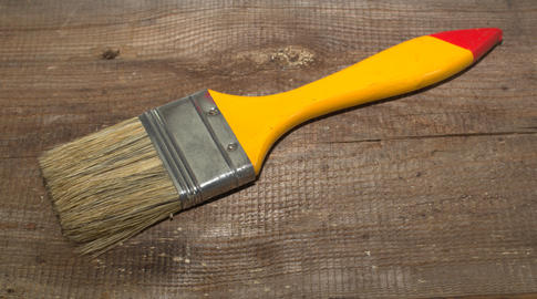 Paint brush width 2 inch with yellow handle on a wooden background Photo