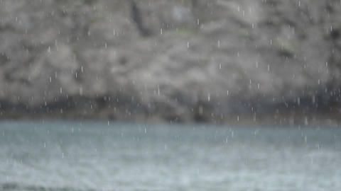 Rain On Calm Sea With Rocks In Background Footage