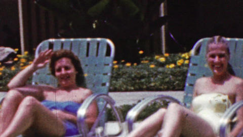 1961: Women suntanning poolside lawn chairs bathing suits lounge Footage