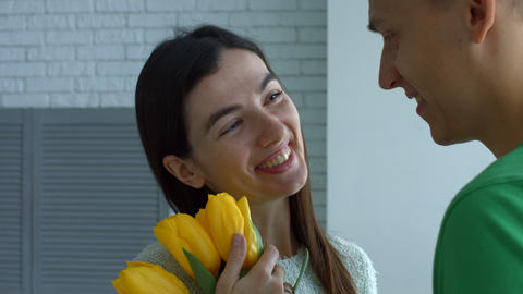 Lovely woman enjoying smell of flowers given by man Footage