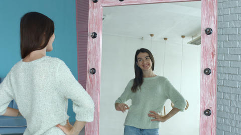Cheerful woman looking at herself reflection in mirror Footage