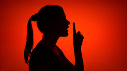 Silhouette of young woman making silence gesture on red background. Concept of Footage