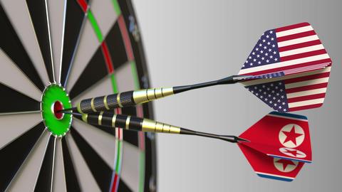 Flags of the USA and North Korea on darts hitting bullseye of the target Footage
