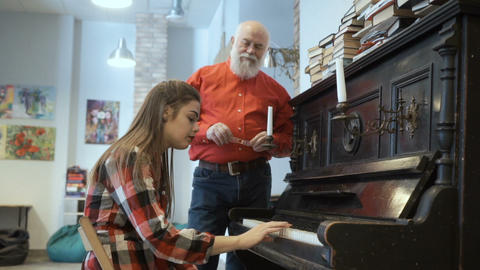 Young girl doesn't get to play well on the piano, the grandpa calms down her Footage