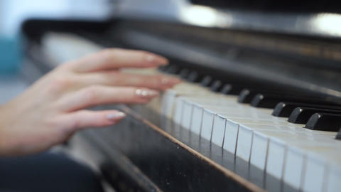 Female hand gently touches piano keys Footage