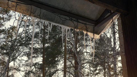 Icicles melt on roof winter gazebo in country village. Snowy icicles and garland Footage