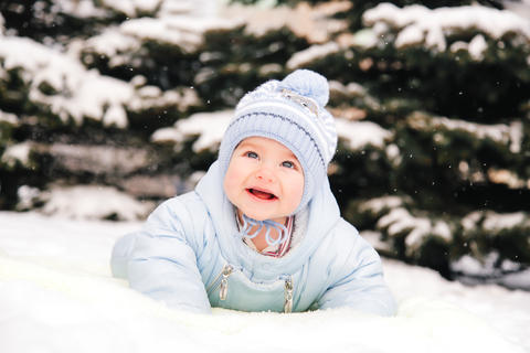 Beautiful baby in overalls lying on the snow and smiling Fotografía