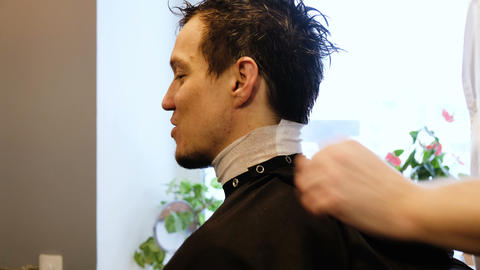 Hairdresser puts on a protective cape apron to a man in a beauty salon Live Action