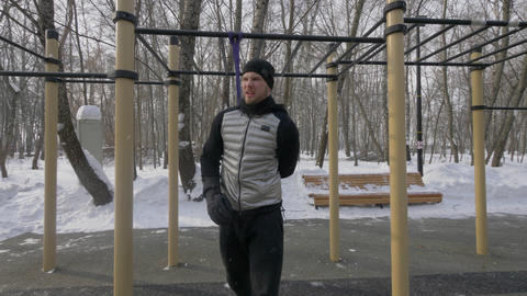 Athlete man doing squat exercise with sport expander on winter sports ground Live Action