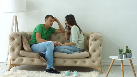 Relaxed couple talking together sitting on sofa Footage