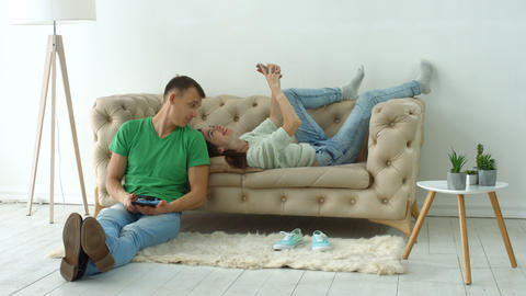 Couple using digital devices on cozy couch at home Footage