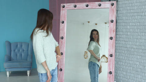 Elegant woman posing in front of mirror at home Footage