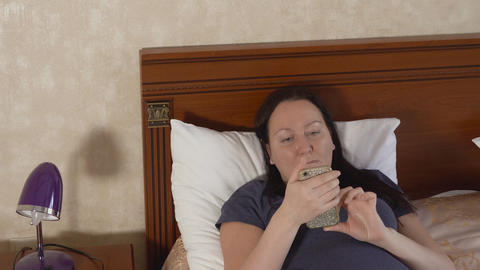 Adult woman lying on bed and browsing social media in mobile phone Live Action