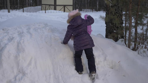 Happy girl climbing on snow hill for funny riding. Happy winter activities Footage