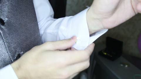 groom in silver vest puts on cufflinks on white shirt Footage