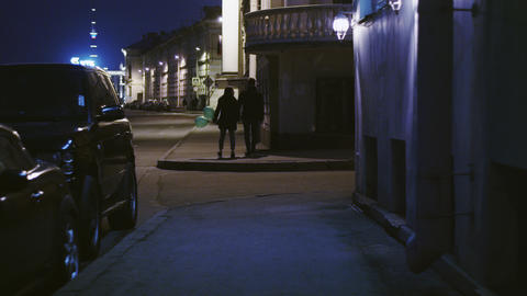 A young couple walking on the night street with air balloons Footage