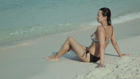 smiling woman sitting on sandy sea beach Footage