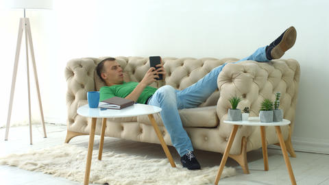 Relaxed man surfing on digital tablet at home Live Action