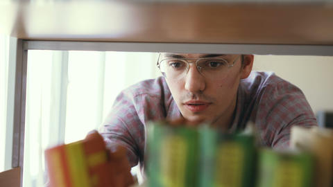 Young caucasian handsome male student is standing in front of bookshelf in big Footage