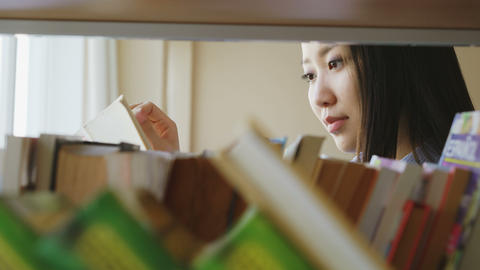Attractive asian student girl standing near shelf with books in university Footage