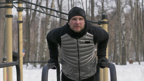 Portrait fitness man doing push ups exercise on bar on winter sport ground Footage
