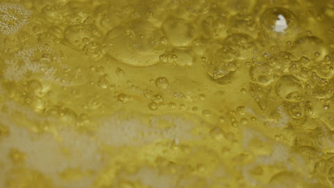 Abstract boiling solid yellow liquid, close up top view Footage