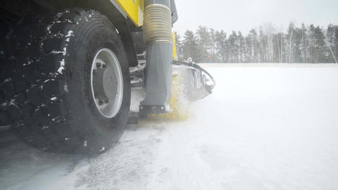 Camera follows the heavy wheel machinery, that removes snow from the road with ビデオ