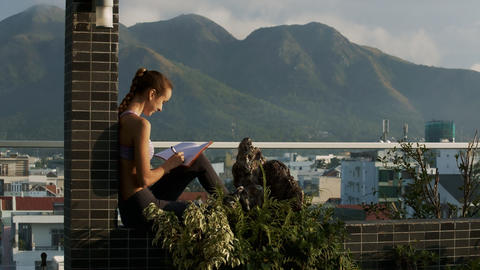Woman Sits on Terrace Writes down Thoughts in Diary Footage