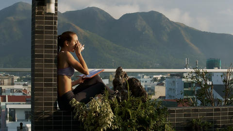 Girl Sits on Terrace Barrier Writes in Diary against Hills Footage