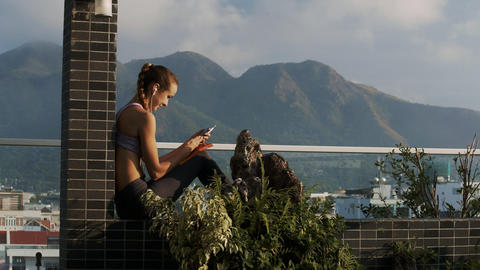 Woman Reads Messages in Phone on Terrace at Hills Live Action
