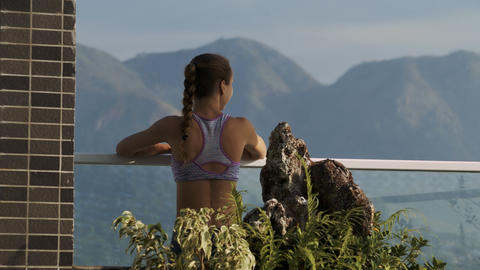 Woman Leans on Terrace Handrail Watching Mountains Footage