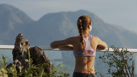 Girl Leans on Glass Wall Handrail Watches Hills Footage