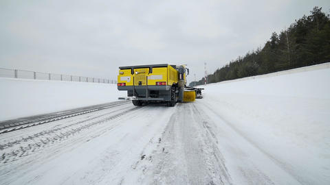 Snow and ice removal truck removes snow from the road with big bucket and Footage