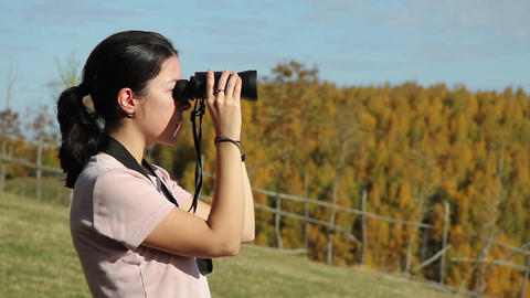 Young woman looks into the distance with binoculars at the edge of a dense decid Footage