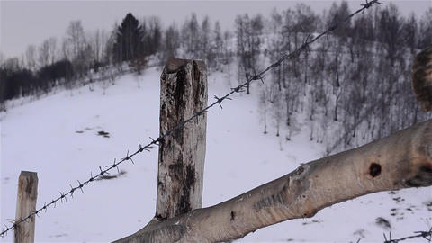 Wooden fence and barbed wire that surrounds a property lying on the snow covered Footage