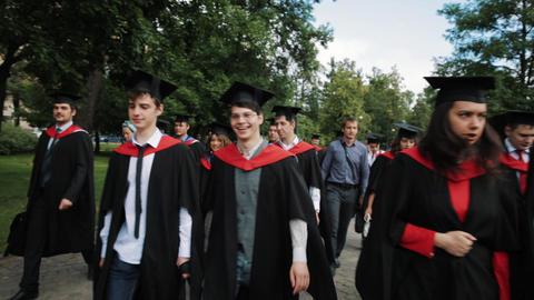 Group of graduating students walking through city park Archivo