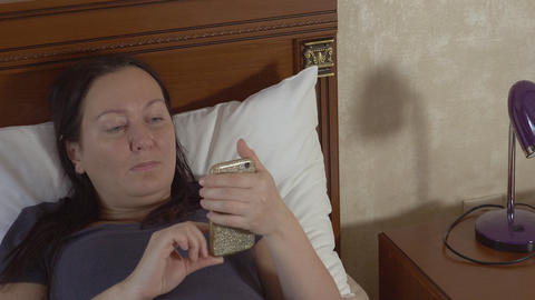 Woman browsing her smartphone and lying in bed Footage
