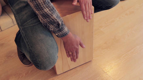 Mans hands to beat off a rhythm on wooden box isdide room Live Action